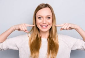 lady smiling pointing to teeth